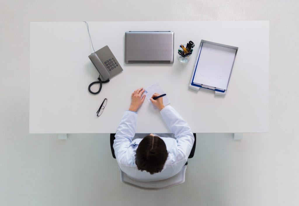 doctor writing prescription at table