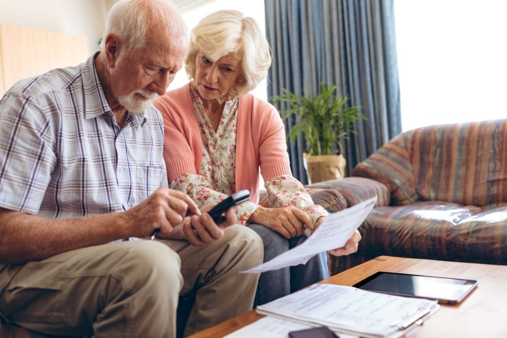 Front view of active Senior Caucasian couple calculating bill while sitting at retirement home